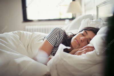 Tired, serene woman sleeping in bed