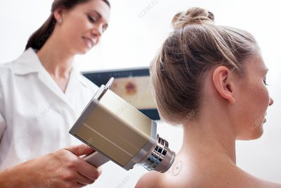 Young woman in skin clinic having mole scanned