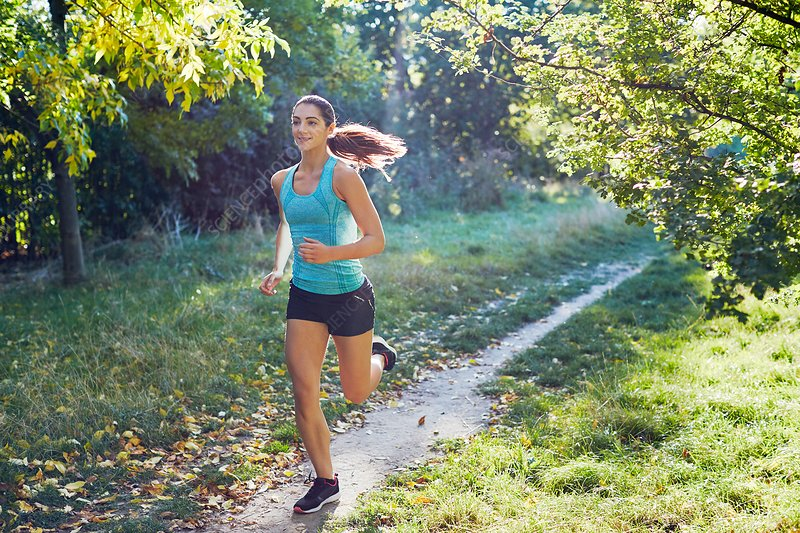 Young woman jogging on path