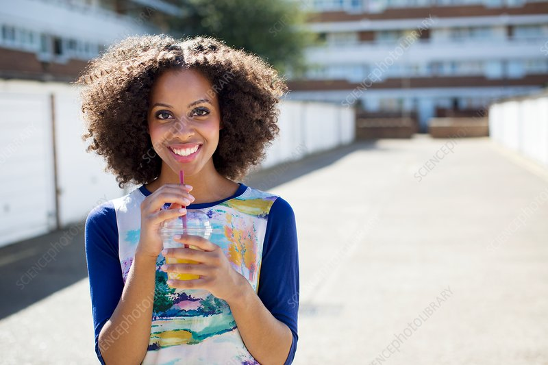 Woman with drink outdoors, smiling