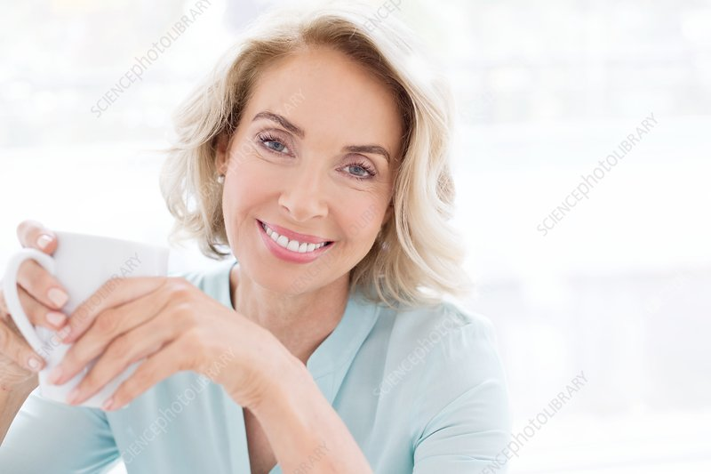 Mature woman smiling with cup of tea