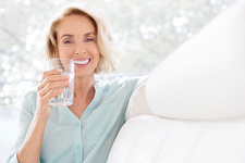 Mature woman smiling with glass of water