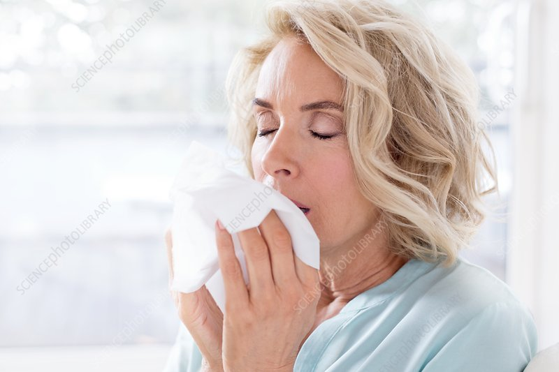 Mature woman blowing nose on tissue