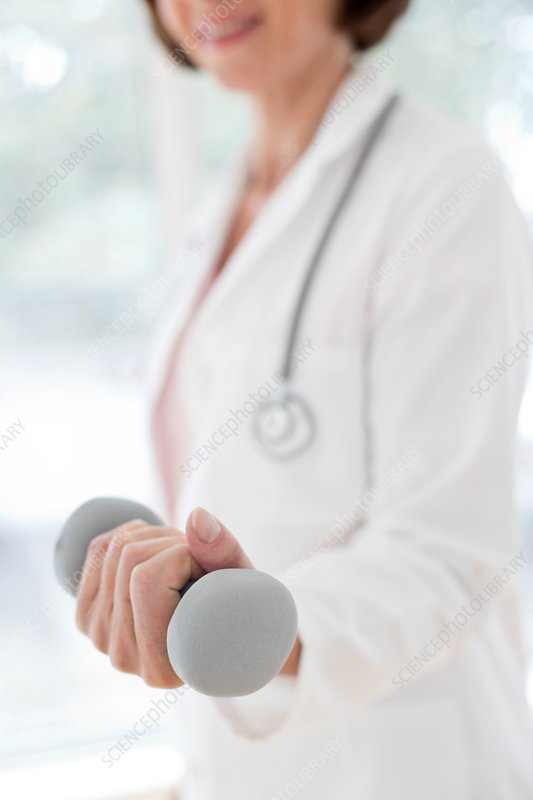 Female doctor holding hand weight