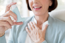 Mature woman using inhaler