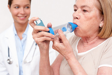 Senior woman using an inhaler, nurse watching