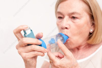 Senior woman using an inhaler