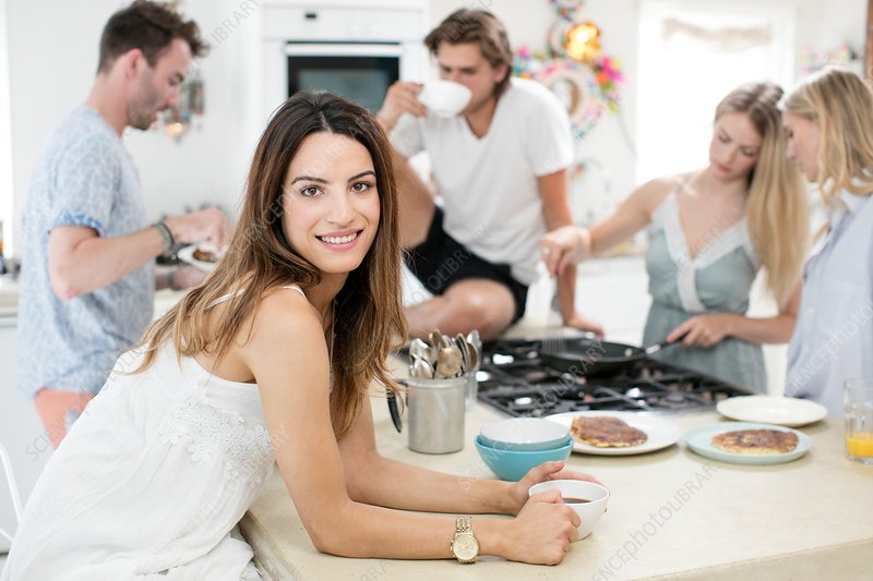 Woman with coffee in kitchen with friends