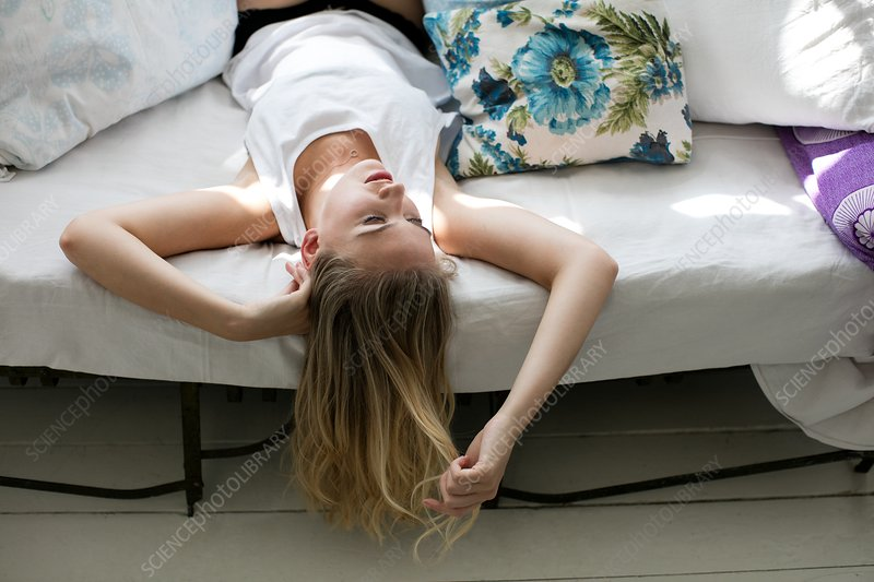 Woman lying on sofa upside down