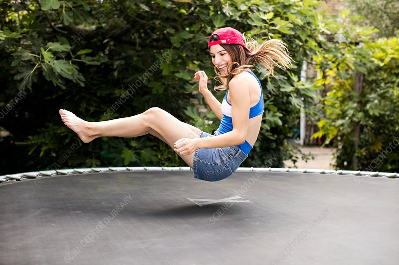 Woman bouncing on trampoline