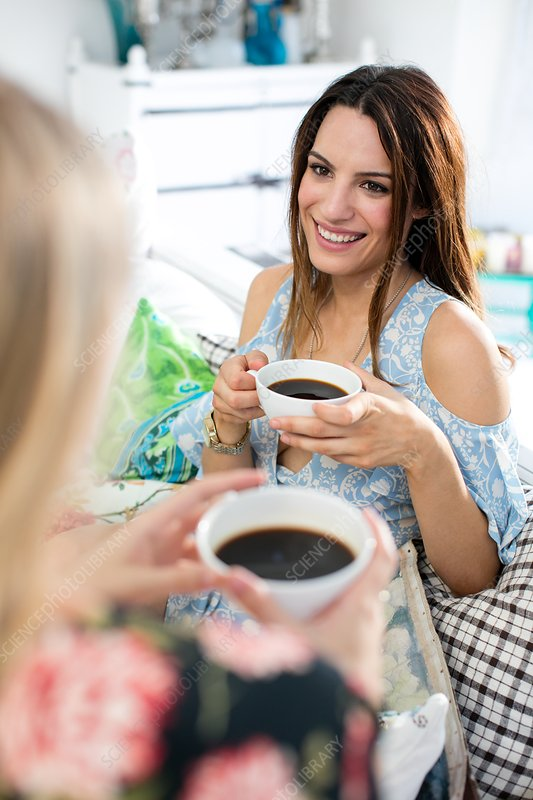 Woman with black coffee talking to friend
