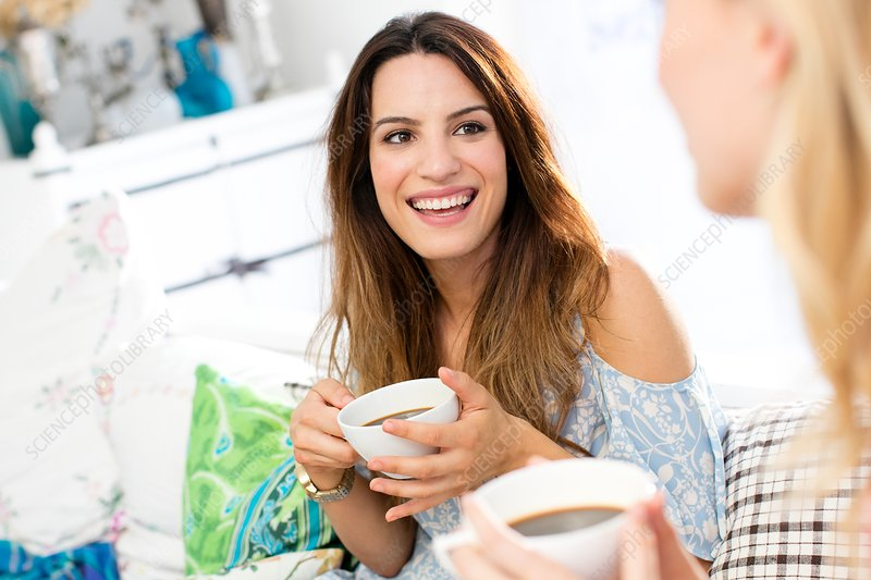 Woman with coffee, talking to friend