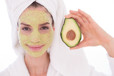 Woman holding avocado with face mask
