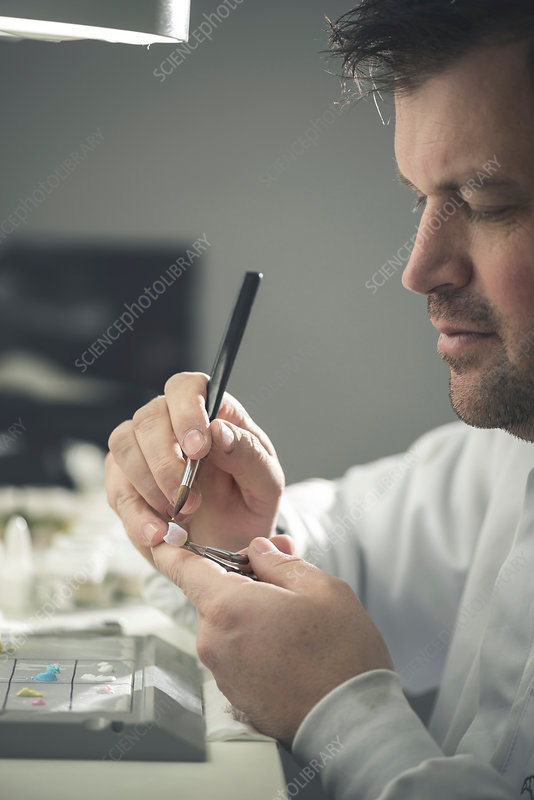 Man working on false tooth