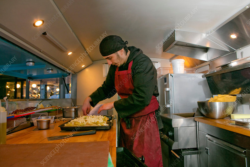 Chef preparing pizza in food stall van at night