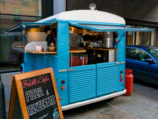 Chef preparing pizza in vintage van
