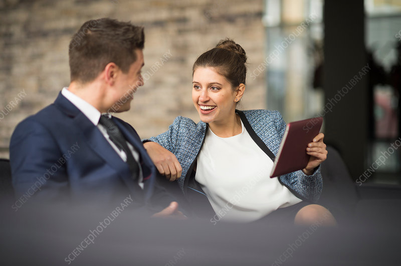 Businesswoman and man meeting on office sofa