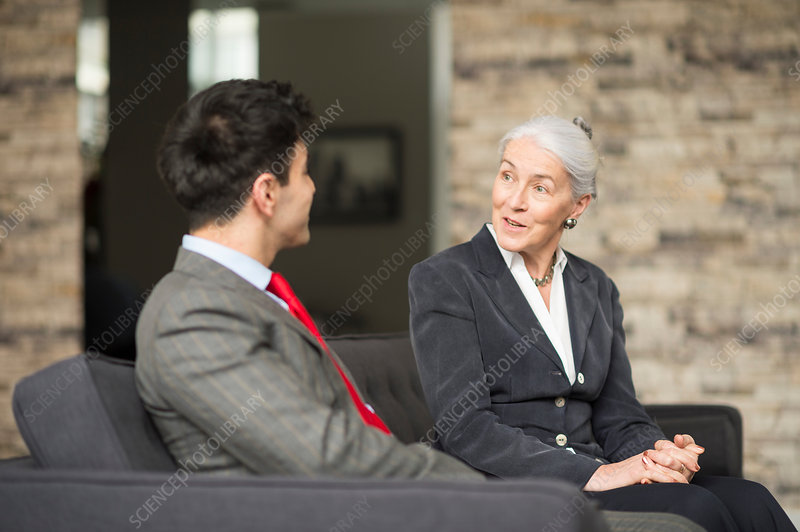 Businesswoman and man having meeting on office sofa