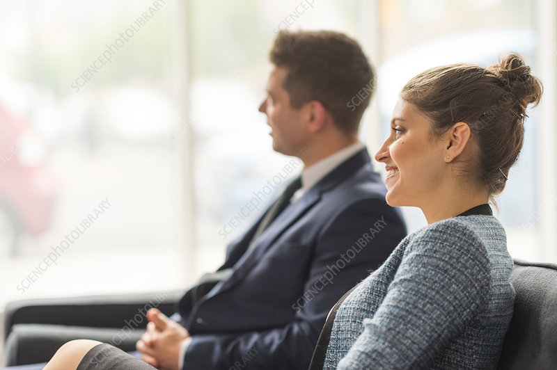 Businessman and woman sitting on sofa in office meeting