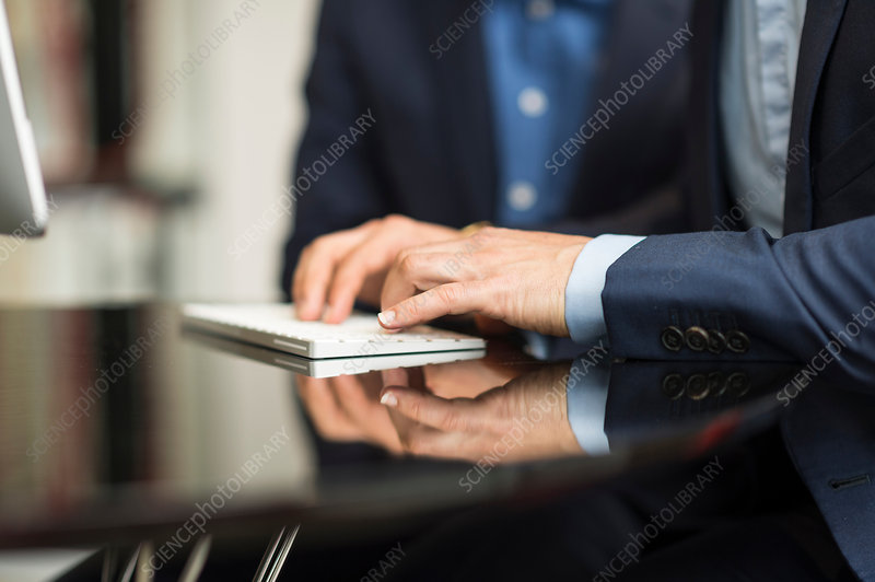 Detail of businessman's hands typing on keyboard