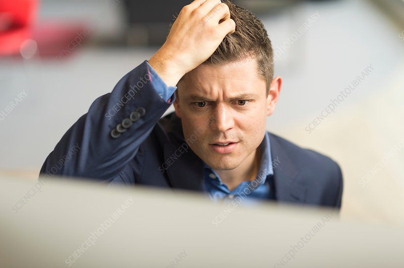 Businessman looking at computer scratching his head
