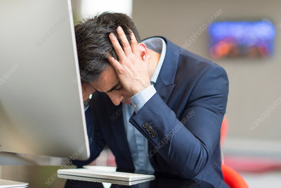 Stressed businessman at office computer with head in hands