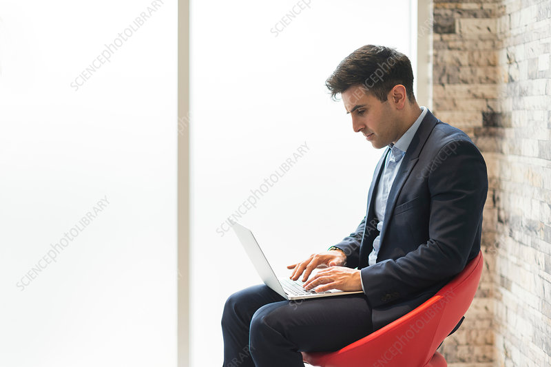 Businessman sitting on office chair typing on laptop