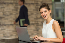 Young businesswoman typing on laptop at office desk