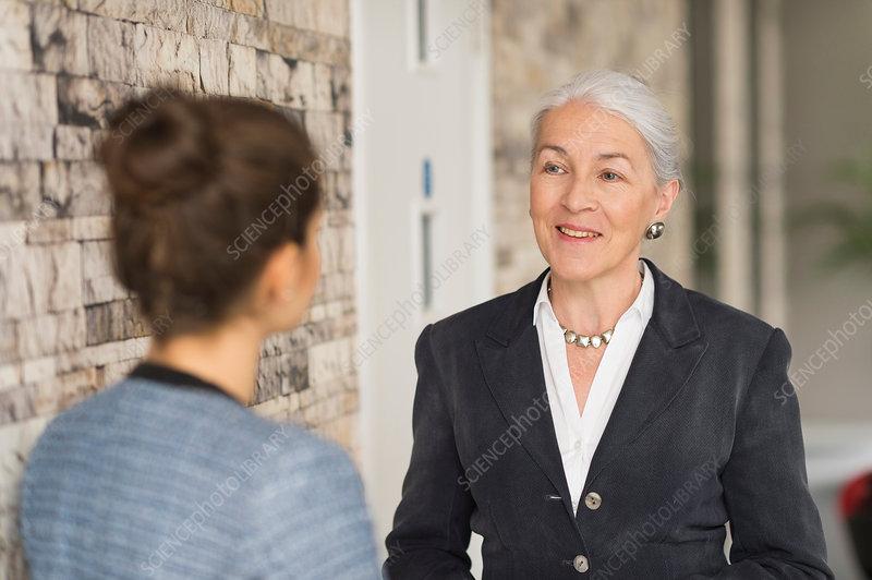 Over shoulder view of businesswomen talking in office