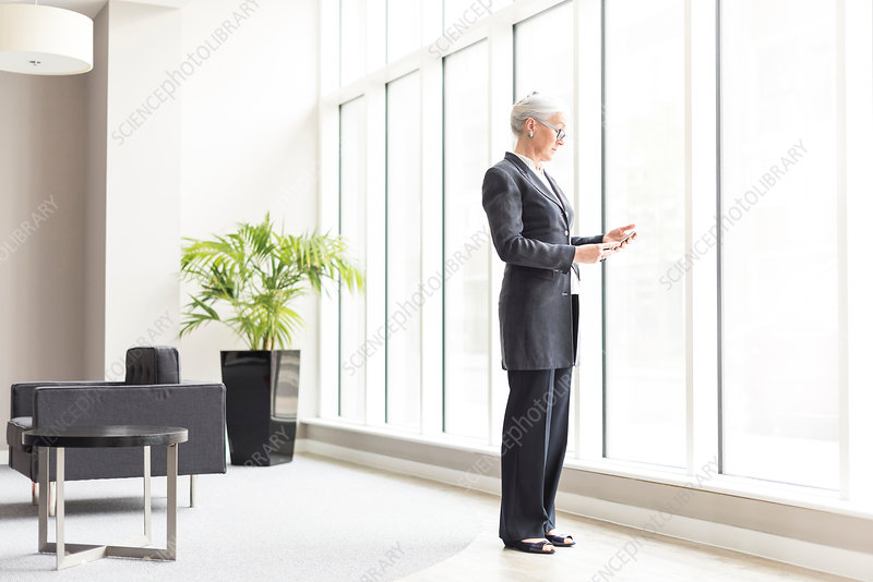 Mature businesswoman looking at smartphone by office window