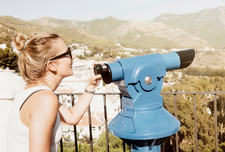 Woman by telescope on viewing platform, Spain