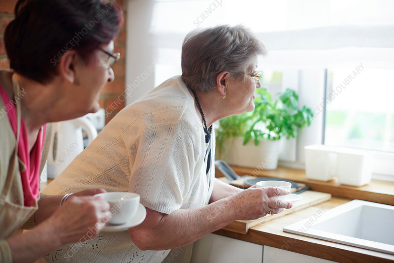 Senior women drinking coffee and peering out of window
