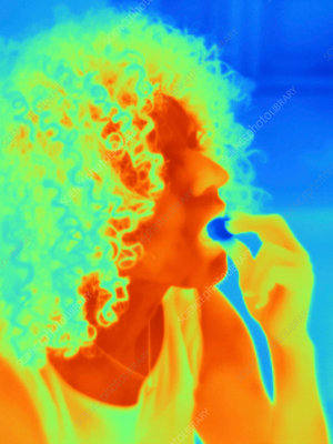 Thermal image portrait of mid adult woman eating