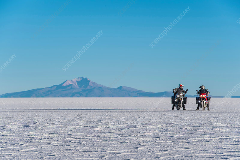 Two men riding motorcycles on salt flats, Bolivia