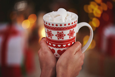 Woman holding hot chocolate in festive mug
