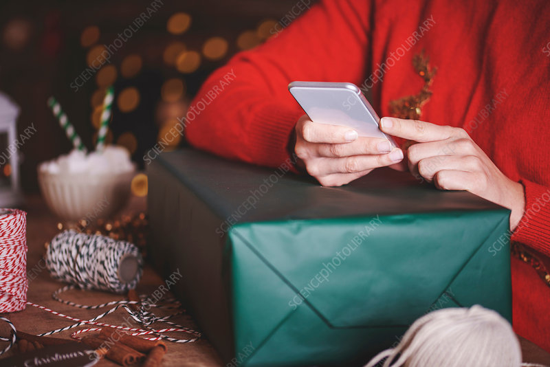 Woman with Christmas present using smartphone