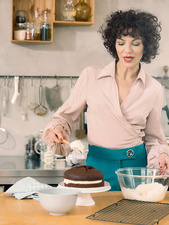 Woman decorating chocolate cake with dairy cream