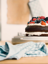 Chocolate cake decorated with cream and fresh summer fruits