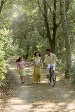 Family with bicycle in forest