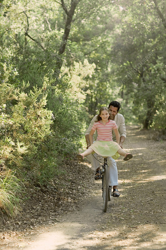 Father and daughter riding bicycle through forest