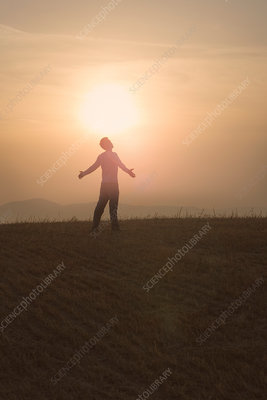 Man standing in field at sunset, arms open