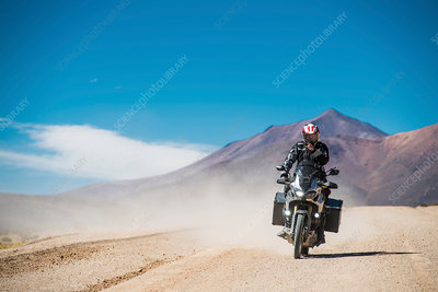 Motorcyclist riding motorcycle on dusty road, Bolivia