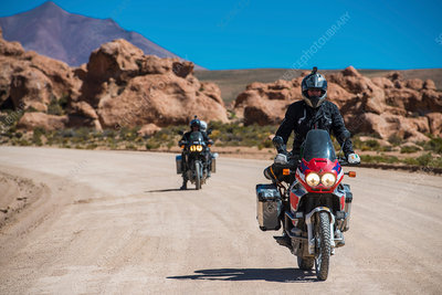 Motorcyclists riding motorcycles on dusty road, Bolivia