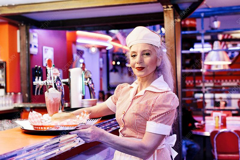 Portrait of mature female waitress in 1950's diner