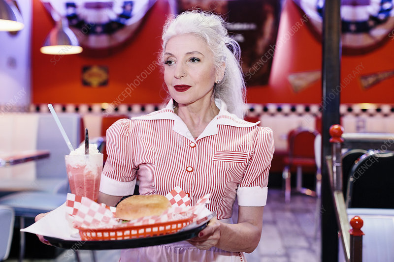 Mature female waitress serving burger in 1950's diner
