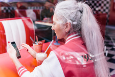 Mature woman in baseball jacket looking at smartphone