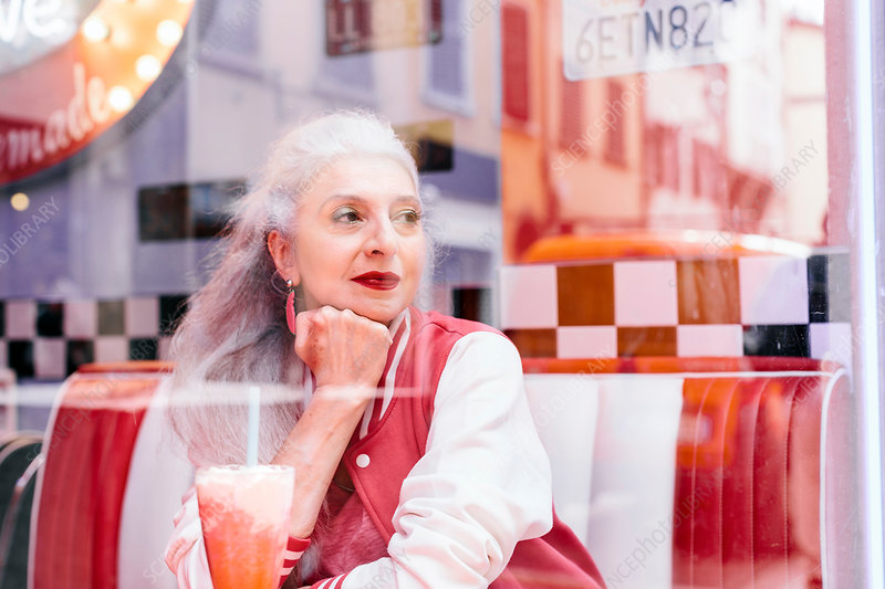 Mature woman looking through window from 1950's diner