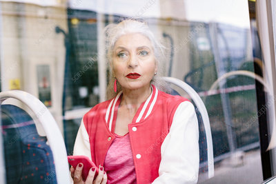 Mature woman looking through window from bus