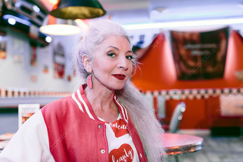 Portrait of mature woman in baseball jacket in 1950's diner