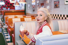 Mature woman with milkshake in 1950's diner